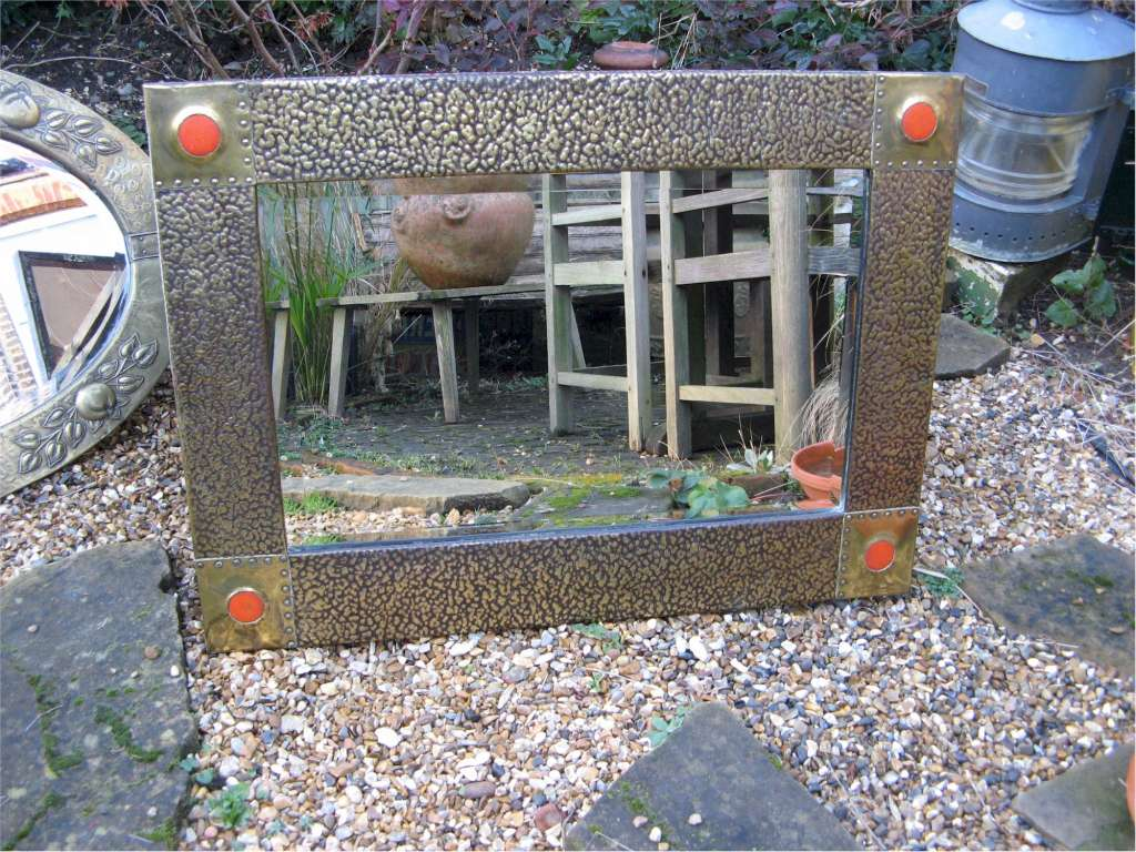 Large arts and crafts hammered  brass framed mirror with orange Ruskin type roundels