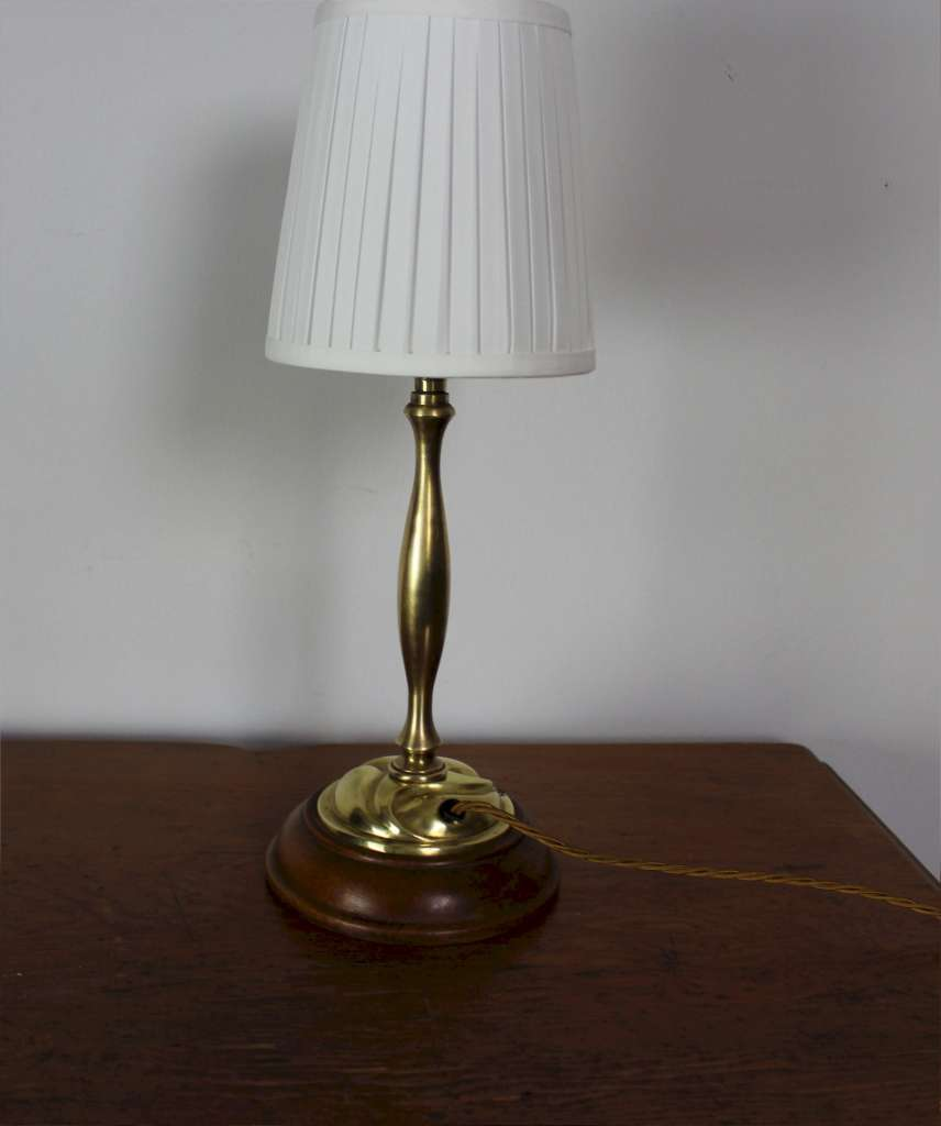 Arts and Crafts brass table lamp on wooden plinth.