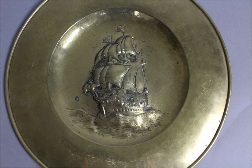 Arts and Crafts brass charger with stylised galleon c1900