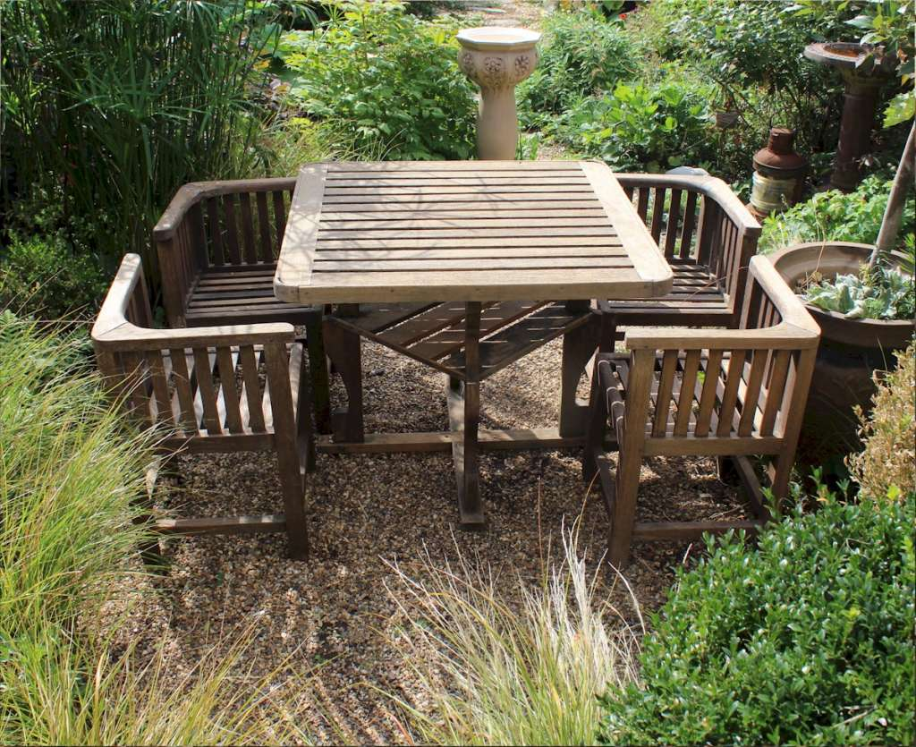 Heals teak garden table and four chairs. c1930