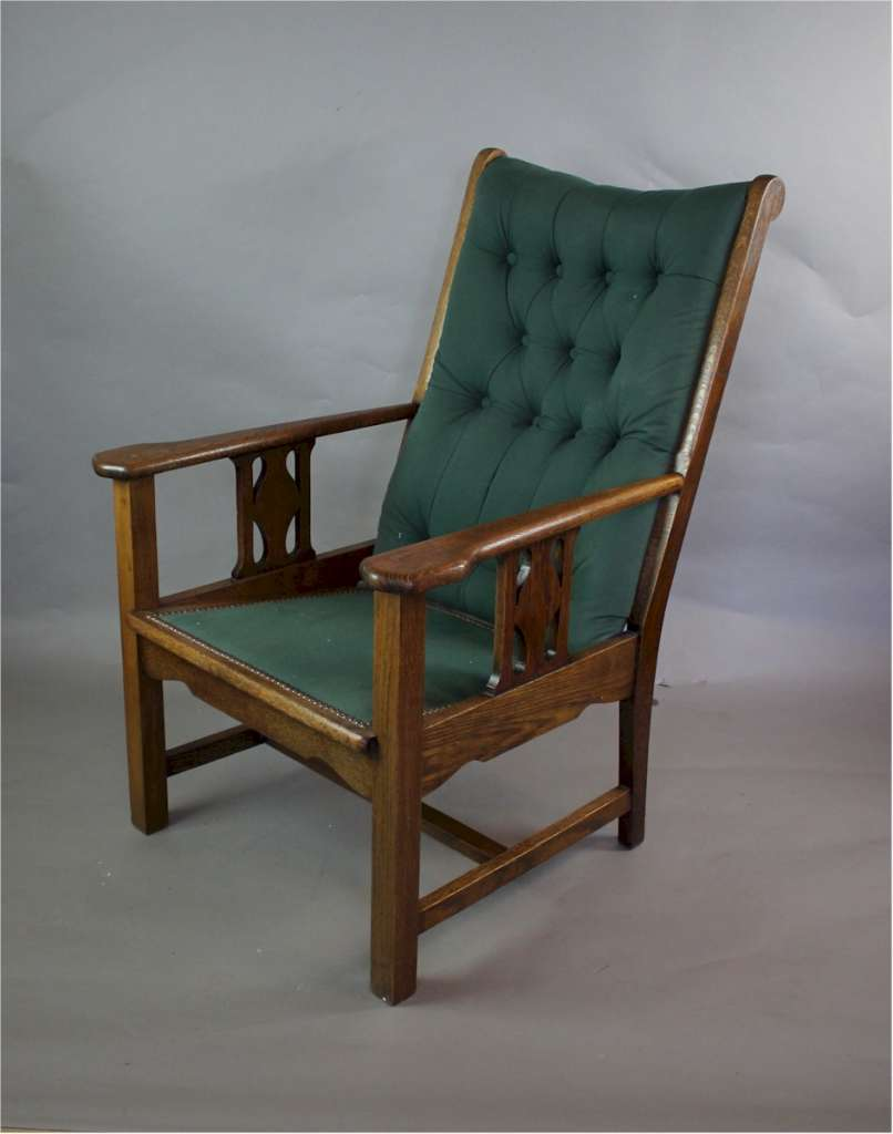 Arts and crafts buttoned back oak framed armchair. c1915
