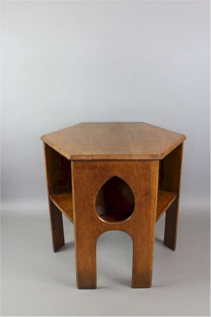 Arts & Crafts hexagonal oak book table with pierced teardrops to three sides and book shelves to the