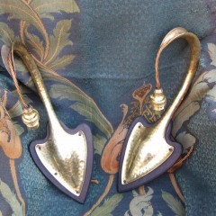Pair of arts and crafts wall lights in hammered brass on wooden heart shaped back