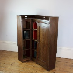 Rare Arts and Crafts Liberty & Co corner bookcase with pierced hearts
