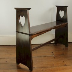 Arts and Crafts window seat by Liberty & Co with pierced heart decoration