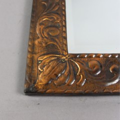 Copper arts and crafts mirror with scrolling leaf design.