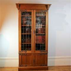 Arts and Crafts glazed bookcase in oak with coppered straps