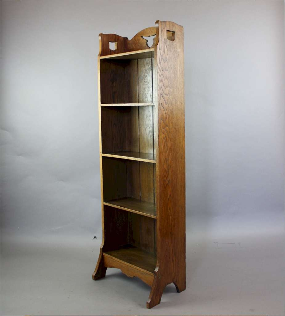 Arts and crafts open oak bookcase with tulip shaped cut-outs